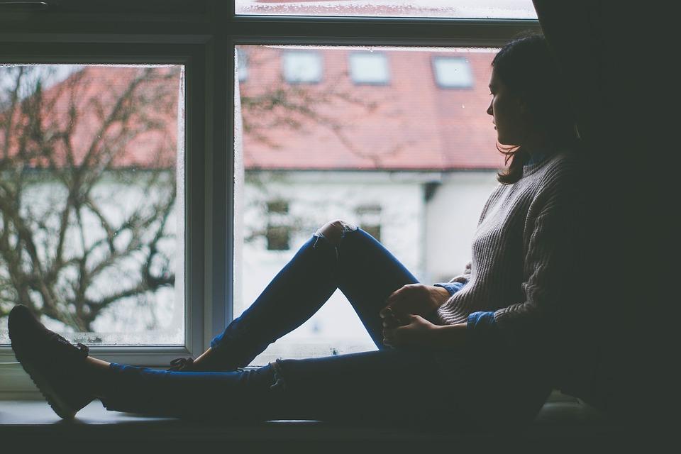 žena hľadí z okna