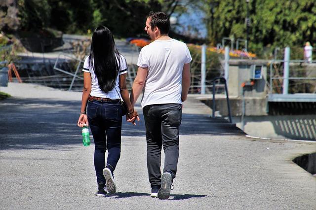 Žena a muž, pár sa drží za ruku, kráča po ulici