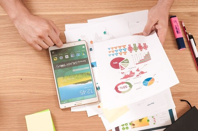 Človek zapína tablet a v ruke drží papiere s grafmi a postavičkami.jpg