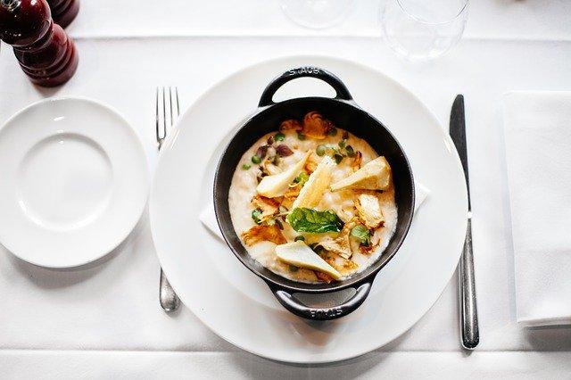 Jedlo v keramickej miske, príbor a taniere na stole.jpg