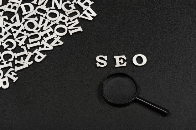 seo-word-written-from-wood-letters-magnifying-glass-black-background-search-engine-optimization_134398-8490